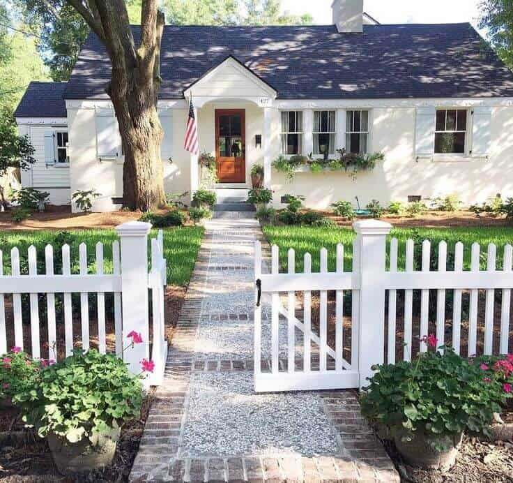 cute cozy white cottage with picket fence