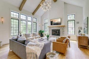 vaulted ceiling with beams fireplace lots of big windows and open concept floor plan living room
