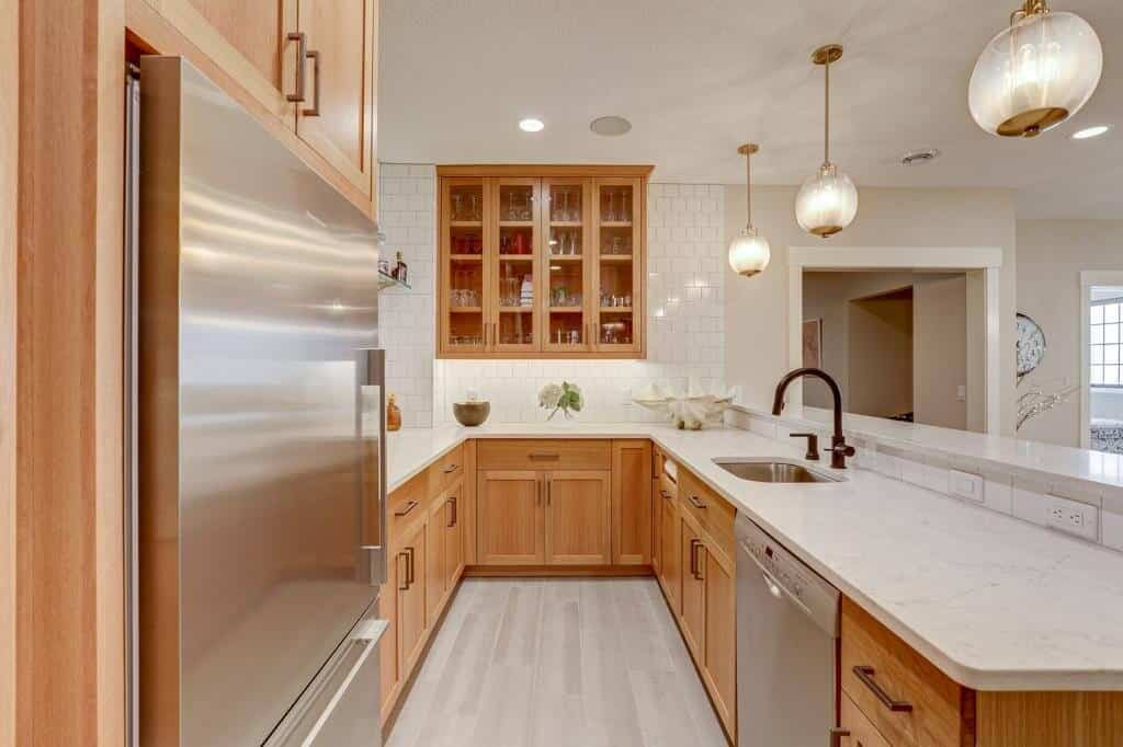 lower level basement kitchen with appliances sink white oak cabinets