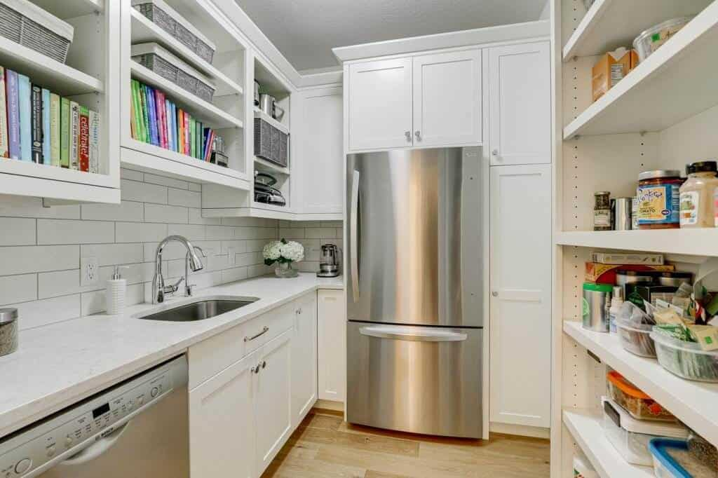 walk in pantry with refrigerator sink dishwasher and lots of cabinets for storage