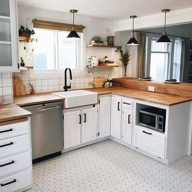 farmhouse kitchen with butcher block countertops white cabinets and pattern flooring