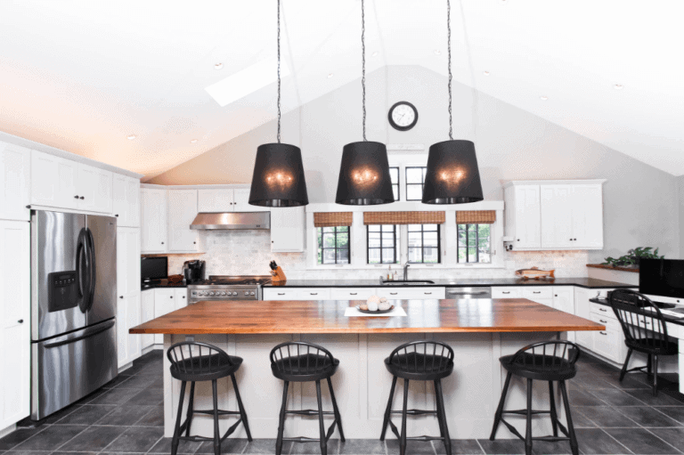 white modern coastal kitchen with butcher block island and dark tile flooring black pendants and accents tie it together