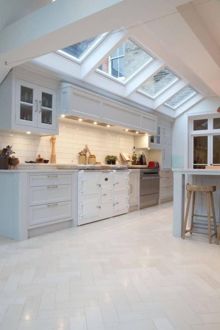 traditional white kitchen with herringbone white tile flooring custom hood and range skylights for added interior light