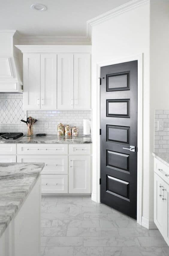 traditional classic white kitchen with marble tile flooring and black pantry door