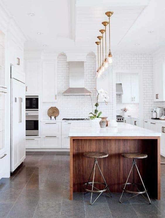 Modern farmhouse white kitchen cabinets wood island with dark grey gray tile floor and white subway tile wall