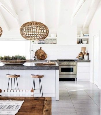 modern white kitchen with white beam ceiling white subway tile wall dark stone countertop and grey gray tile floor wicker globe pendants