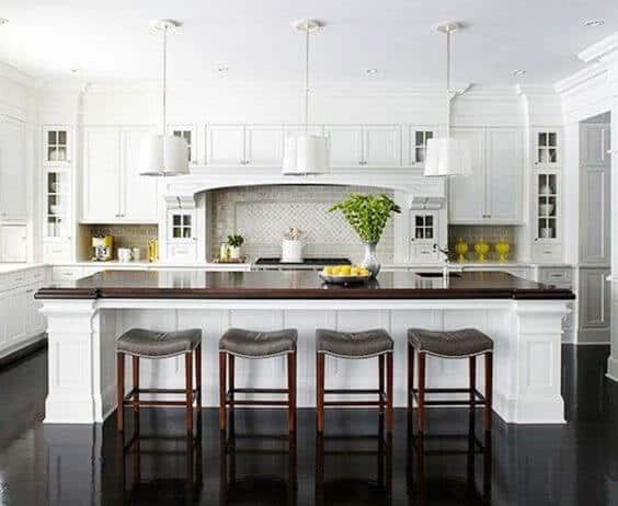 Traditional classic white kitchen cabinets and island with black smooth shiny flooring