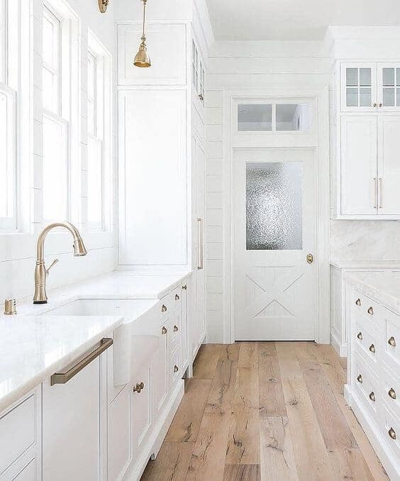 Modern Farmhouse white kitchen cabinets and sink with brass hardware and fixtures natural light wood plank flooring