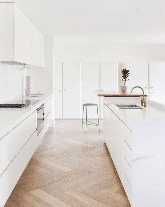 modern all white kitchen with no hardware cabinets and natural white oak herringbone flooring