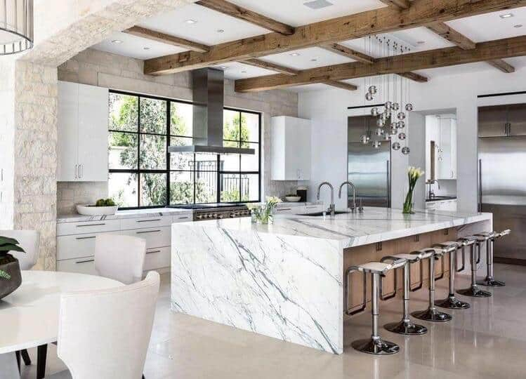 modern farmhouse white kitchen with waterfall marble island reclaimed wood beam ceiling details and brick accent wall next to black windows and modern light flooring tile