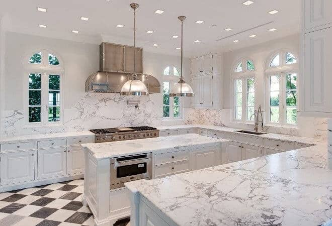 Luxury white kitchen with white marble countertop and backsplash using checkered flooring marble tile and custom polished hood