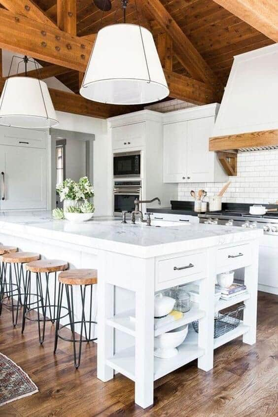 white modern farmhouse kitchen with wood floors white cabinets white subway tile and wood beam ceilings