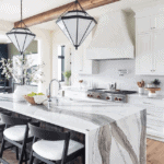 Quartz waterfall island countertop in modern tudor new house with white kitchen and pendant lighting