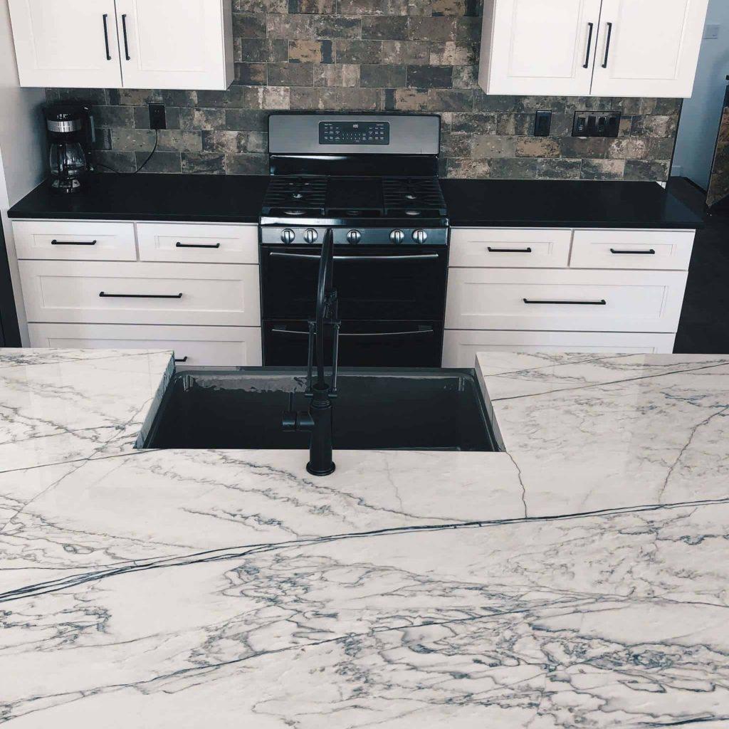 White Macaubus Countertop Island and Honed Black Granite Perimeter with gray grey farmhouse sink and matte black brizo faucet