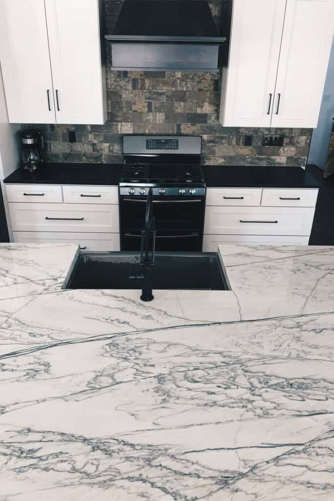 White Macaubus Countertop Island and Honed Black Granite Perimeter with gray grey farmhouse sink and matte black brizo faucet