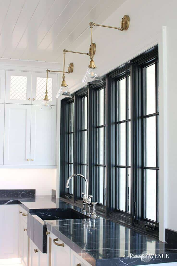 Black Marble countertop and sink in white French Country Luxury Kitchen with all white island