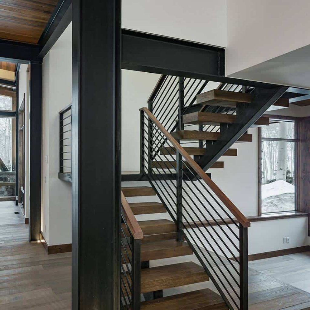 modern floating staircase with wood open treads and a single central metal stringer. has metal railing with top wooden rail. c channel beams supports second floor and add industrial feel to this mountain home