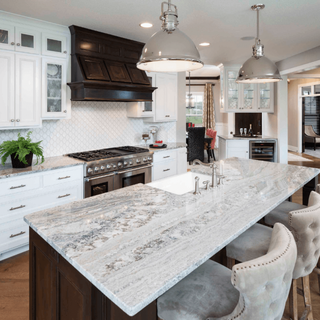 A beautiful granite countertop with hints of blue and brown make it a perfect match for a traditional or farmhouse white kitchen. The hints of brown are pulled with the dark stained range wood hood. Mont Bleu Polished Granite is always a great choice for your countertop.