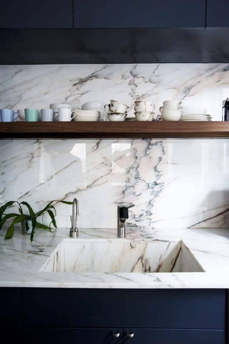 Pink hued marble make a stunning countertop, sink and backsplash in this modern kitchen. Brushed chrome faucets, open shelving and dark navy cabinetry / joinery complete the luxurious design.