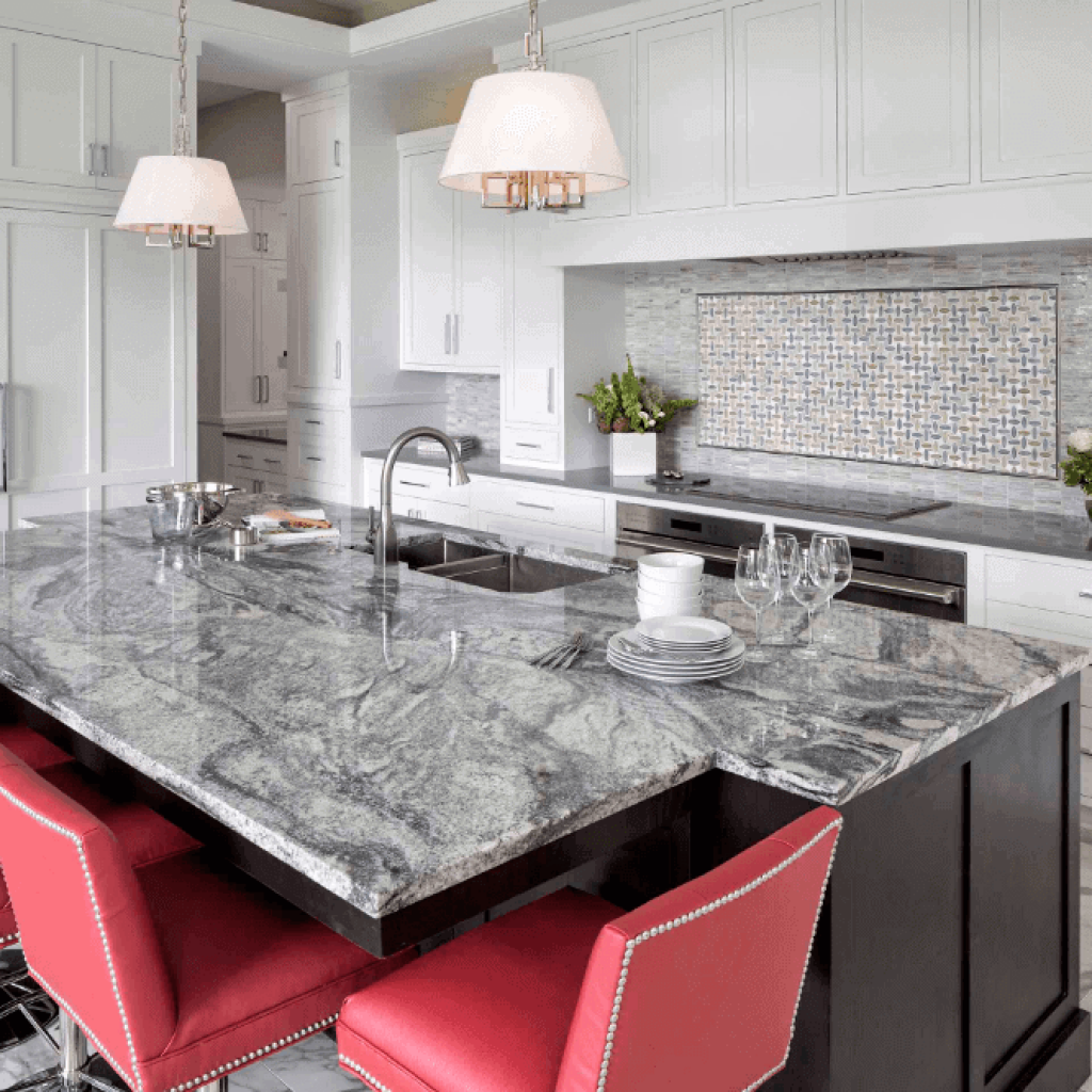This salone grey and white granite adds the perfect grey cool tone to this traditional yet slightly modern kitchen. This granite has lots of movement, swirls and depth which is a great contrast against the bright red island seating.