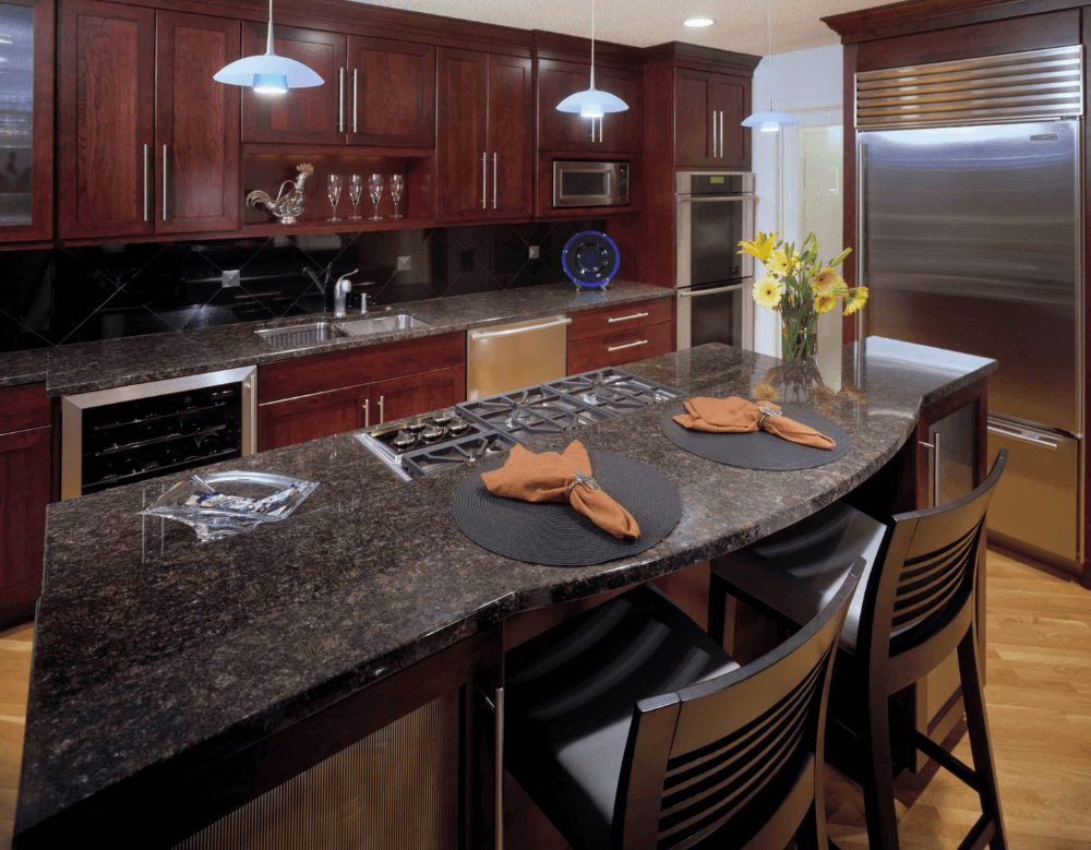 A beautiful tan and brown polished granite countertop that is set on gorgeous cherry cabinets. Stainless steel appliances and chrome fixtures complete the traditional kitchen style.