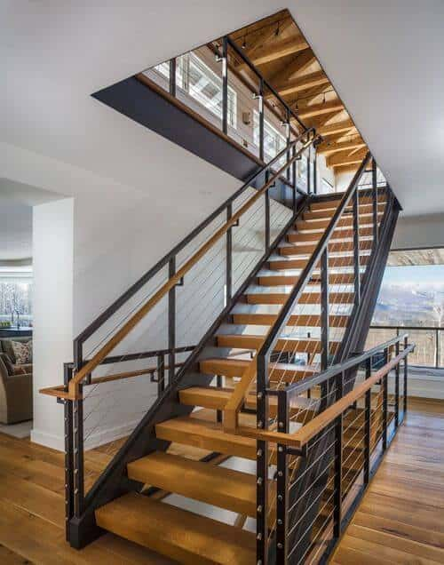 A modern open tread staircase with natural colored wood treads and black steel beam stringers provide access to the second and basement floors. Railing is a combination of metal, wood and cable system.