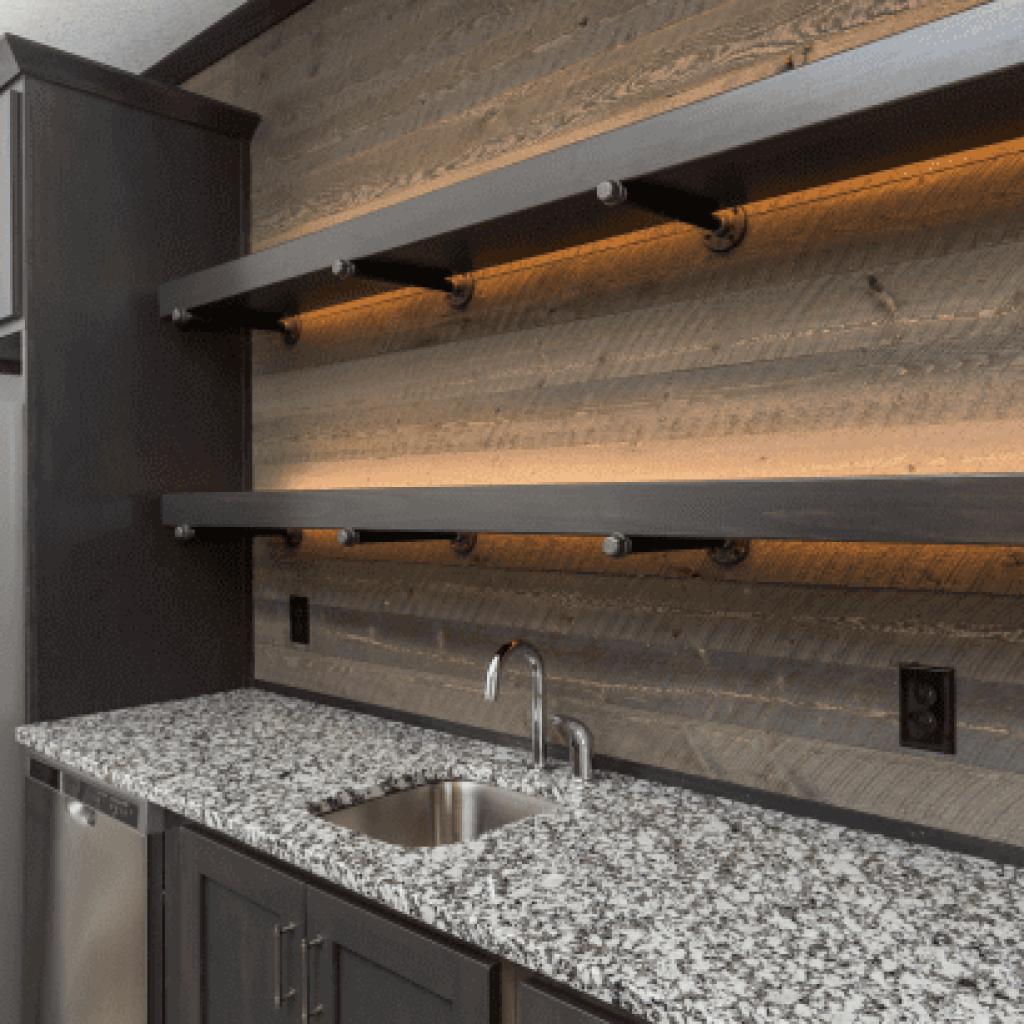 A grey and white polished granite makes a perfect countertop for a basement wet bar. Set with dark lower cabinets, open shelving and a reclaimed wood wall makes for a perfect lounge area.