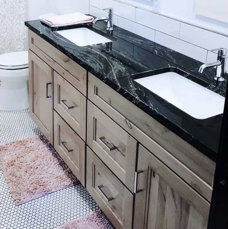 Black Granite with white accents polished bathroom countertop and black and white penny tile with natural alder cabinets