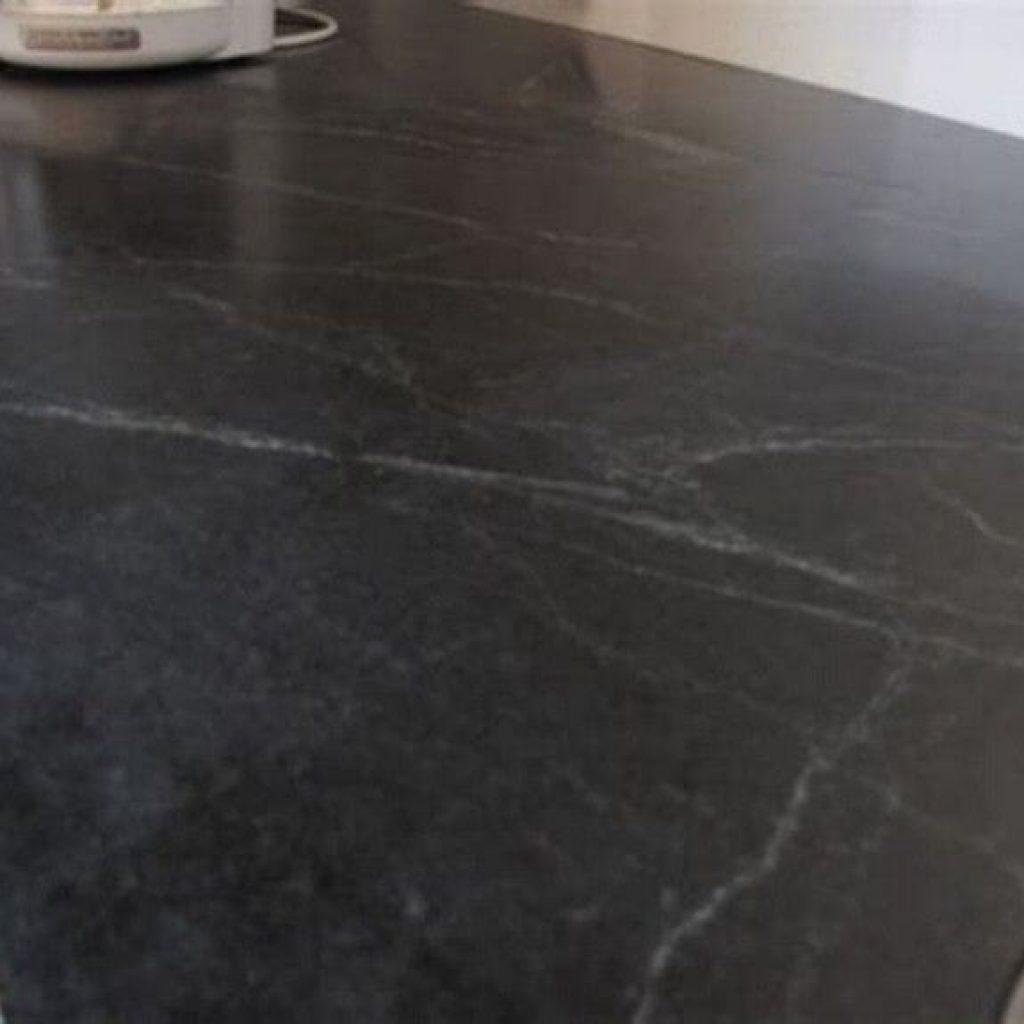 Black honed granite with soft white movement swirls in it.