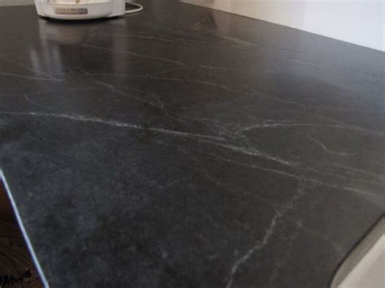 Black honed granite with soft white movement swirls in it.