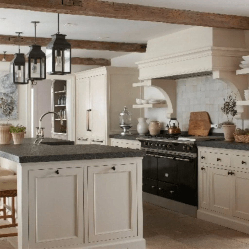 A classic white cabinet kitchen with black granite countertops and reclaimed wood beams on the ceiling. Lantern lighting over the island tops off this classic farmhouse kitchen style.