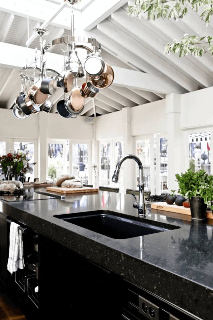 Black granite countertop with thick edge on top of black countertops makes a great contrast to the white walls, ceiling and windows of this open concept kitchen.