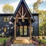 A gorgeous dark modern farmhouse exterior with contrasting natural wood in a dramatic pitched roof entryway make this home a showstopper! Home by Carbine & Associates. #downleahslane #blackhouse #blackhome #darkexterior #darkhouse #entryway #coveredporch #customhome #luxuryhouse #dreamhome #vaultedceiling