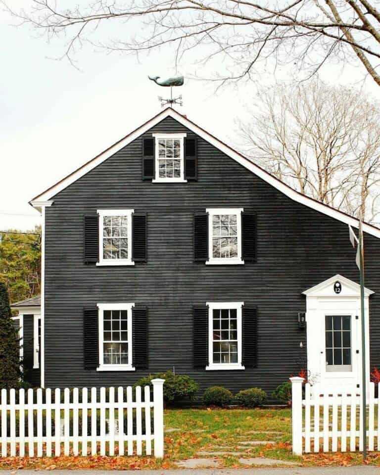A charming black farmhouse with white window trim and a white picket fence create the perfect exterior that is unique and inviting all at the same time. #downleahslane #blackhouse #whitetrim #whitepicketfence #exteriorcolor #exteriorideas #blackshutters #farmhouse #blackfarmhouse #exteriordesign #farmhouseexterior