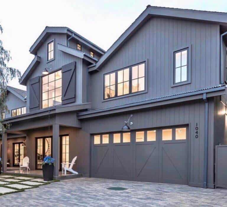 Dark grey, almost black custom home with design features like a barn. Barn door shutters, roofline, board and batten vertical siding and barn like grid windows. The interior light shines through the numerous windows making this a very inviting home.