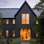 A dramatic dark modern farmhouse with board and batten siding and tan windows with grids. The steep pitch to the gable and steel roof add the finishing touches to this modern exterior. #downleahslane #darkhouse #exteriordesigns #exteriorideas #blackhouse #blackexterior #blackhome #modernfarmhouse #tanwindows #steelroof #modernexterior