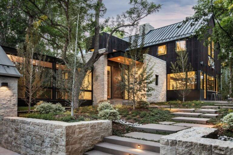 A luxury dark modern farmhouse with beige stone creates a stunning feel to this dream home. This home was nominated for Home of the Year and was designed by Surround Architect, built by Morningstar Home and pic by Jensen Walker. #downleahslane #darkhouse #dreamhome #luxuryhome #stoneexterior #exteriorcolor #homeoftheyear #barndominium #barnhouse #ranchhouse #steelroof #blackhouse #exteriorideas #exteriordesigns