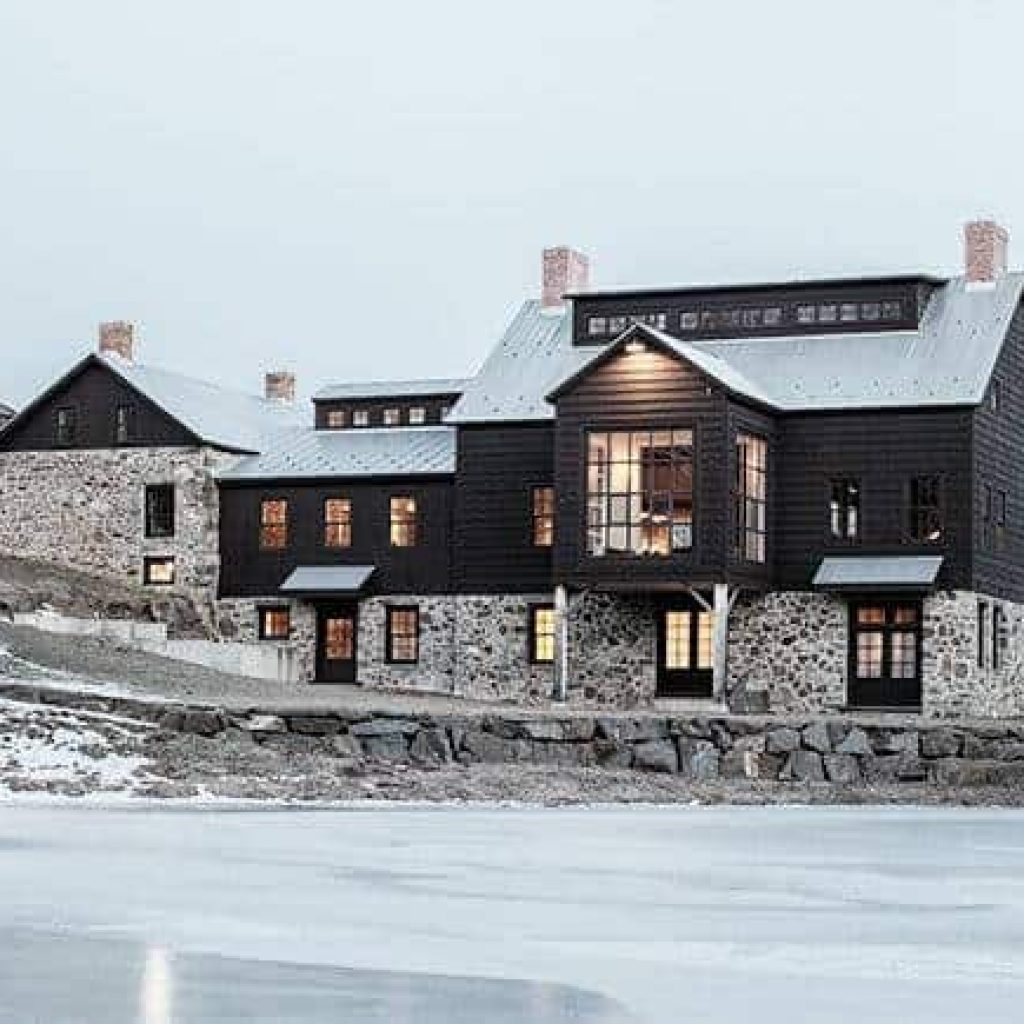 Original Dutch stone and black house is connected with the salvaged vintage barn addition to its right both horizontally and vertically. It contains the entry as well as the stair system which connects three of the four levels of the house. Builder: Gary Lowe. Photo: scott benedict practical(ly) studios. #downleahslane #blackbarn #historicbarn #barndominium #stonehouse #barnhouse #blackhouse #blackexterior #darkhouse #darkexterior #dreamhome #dreamhouse #luxuryhome