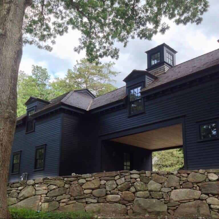 Beautiful dark modern farmhouse exterior with cupola accents and car port to add to the charm. Black siding color with black windows and doors adds drama to this custom home. Via David Dumas Architecture. #darkhouse #darkexterior #blackhouse #blackexterior #cupola #modernfarmhouse #carport