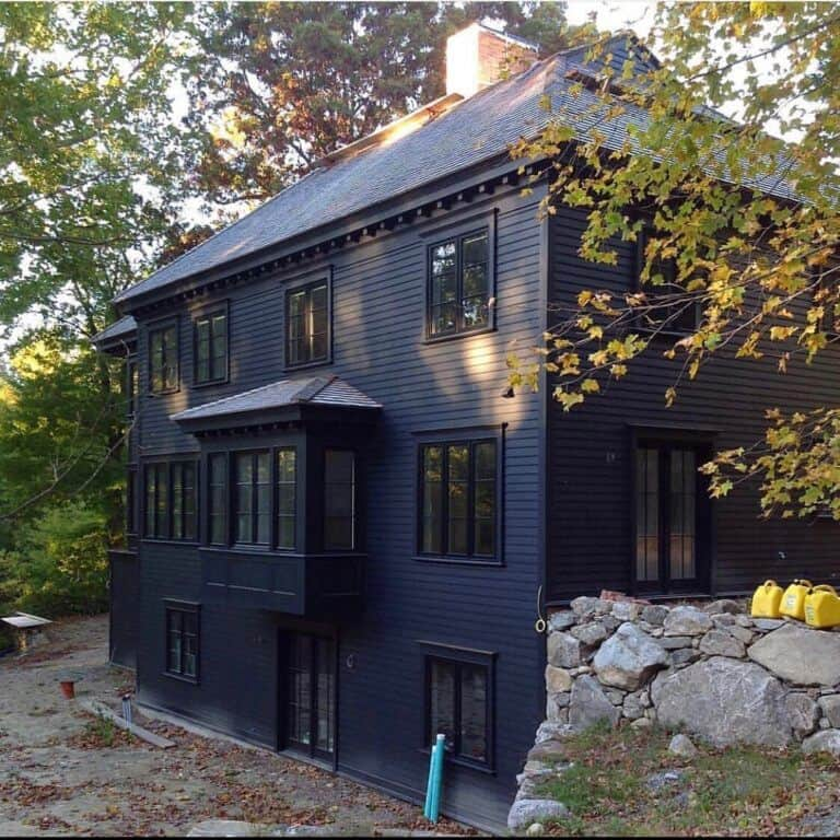 Beautiful dark modern farmhouse exterior with cupola accents and carport to add to the charm. Black siding color with black windows and doors adds drama to this custom home. Via David Dumas Architecture. #downleahslane #darkhouse #darkexterior #blackhouse #blackexterior #cupola #modernfarmhouse #carport