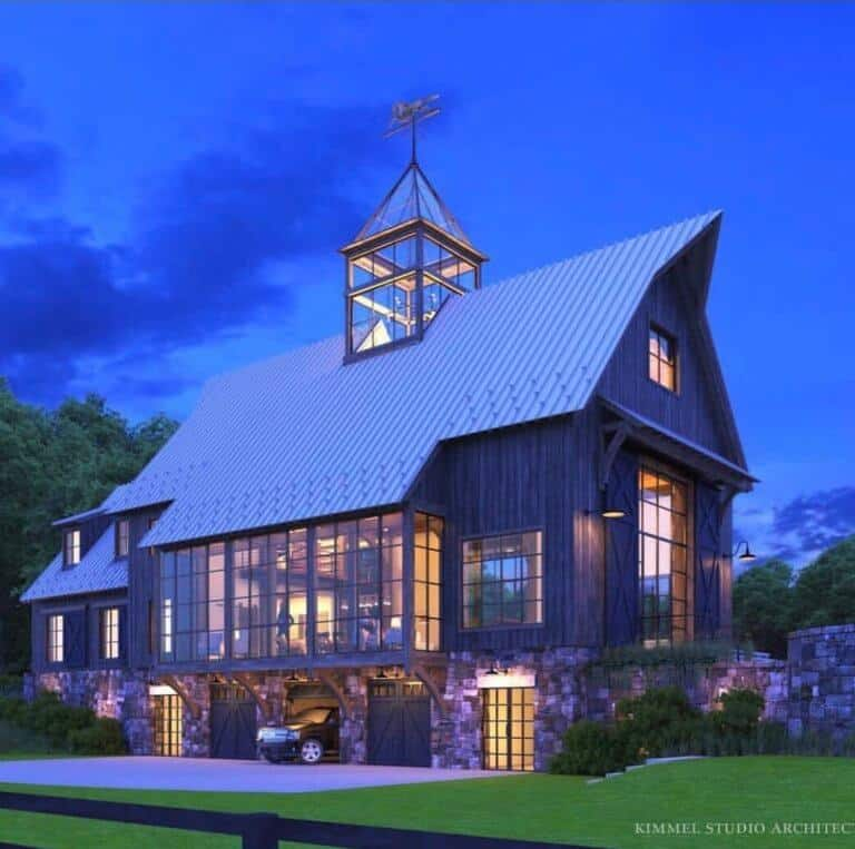 An absolutely stunning dark barndominium with a large glass cupola on top, dramatic huge windows and a steel roof complete this show stopping luxury home!! By Kimmel Studio Architects. #downleahslane #barndominium #cupola #luxurybarn #barnhouse #darkhouse #darkexterior #hugewindows #steelroof #barnhome #dreamhouse #dreamhome #luxuryhome #reclaimedwood