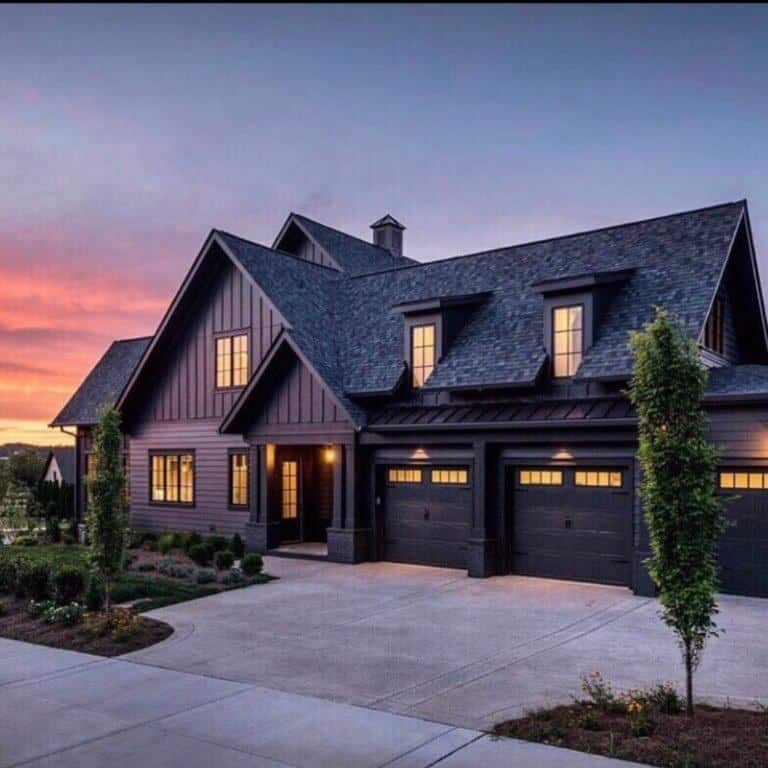 Stunning black house with board and batten siding, black windows and black doors adds drama to this exterior. Constructed by Legend Homes, photo by Reed Brown.