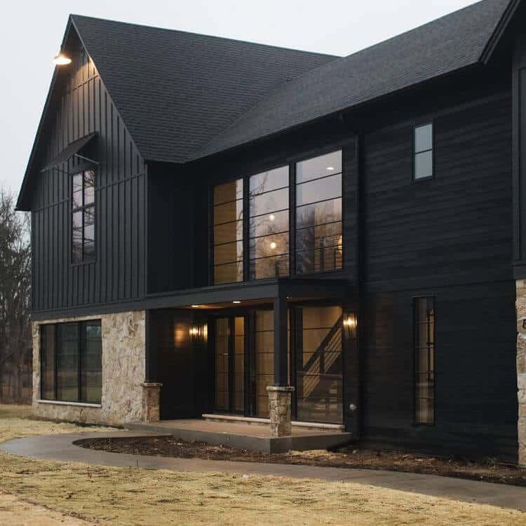 A stunning example of a black modern farmhouse with contrasting beige stone, huge black frame windows, board and batten mixed with horizontal siding and clean lines finish off this modern exterior!! House by M House Development. #downleahslane #blackhouse #modernfarmhouse #modernexterior #darkexterior #darkhouse #dreamhouse #luxuryhome #blackwindows #boardandbatten #exteriorideas #exteriordesign