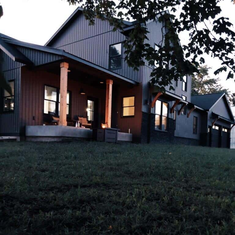 A distinct dark modern farmhouse with clean lines, board and batten black siding, black trimless windows and mirroring covered porches with cedar posts and cedar corbels on eyebrows. The black steel and black shingle roof add to the modern dark look of this farmhouse. Down Leah's Lane's Dark Modern Farmhouse. #downleahslane #darkfarmhouse #darkhouse #modernfarmhouse #modernhouse #blackhouse #blackfarmhouse #coveredporch #cedarposts #blackwindows #attachedgarage #exteriorcolors