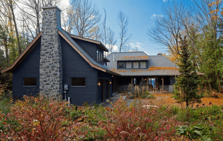 A black cabin perfectly nestled in the fall leaves with a contrasting stone fireplace makes a picture perfect cozy home setting. #downleahslane #blackhouse #darkexterior #darkcabin #stonefireplace #blackcabin #mountainlodge #darklodge #darkhouse
