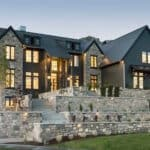 This luxury home features a dark exterior with contrasting stone for a dramatic look any homeowner and architect would dream of. By Raykon Construction. #downleahslane #darkhouse #luxuryhome #blackhouse #darkexterior #stone #dreamhouse #dreamhome #luxuryhouse #stonelandscaping #mansion