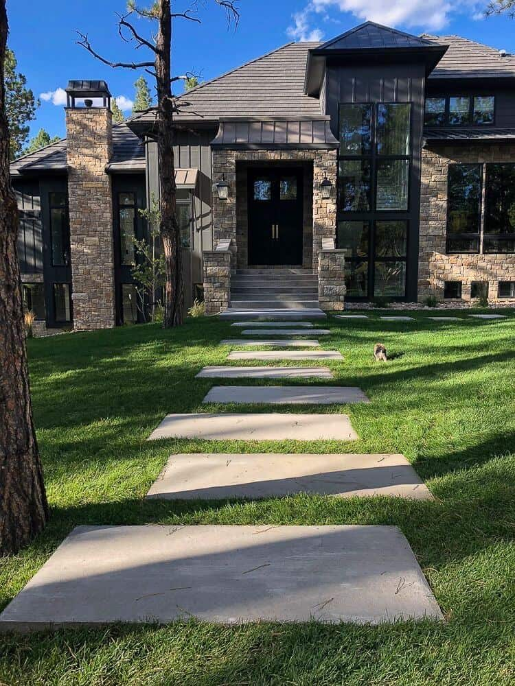 This gorgeous dark modern farmhouse exterior is complemented with tan stone accents, board and batten siding and huge black windows that let in the mountain light and views, by The House of Silver Lining. #downleahslane #darkexterior #modernfarmhouse #blackhouse #dreamhome #luxuryhouse #tanstone #blackwindows #mountainhouse #exteriorideas #exteriordesign