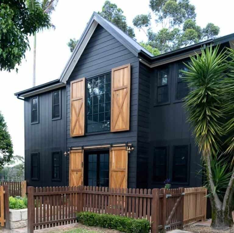 Pairing a black exterior with natural cedar wood shutters provides a great contrast to this dark modern farmhouse. Plus the sliding barn doors on the first floor are amazing! via The Essential Detail. #downleahslane #blackhouse #darkhouse #blackexterior #blackhouse #cedarshutters #slidingbarndoors #cedar #modernfarmhouse #twostoryhouse #dreamhouse