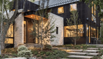 Dream House exterior features modern lines in the dark vertical siding mixed with rustic light white stone nestled in the trees with stone landscape surrounding it