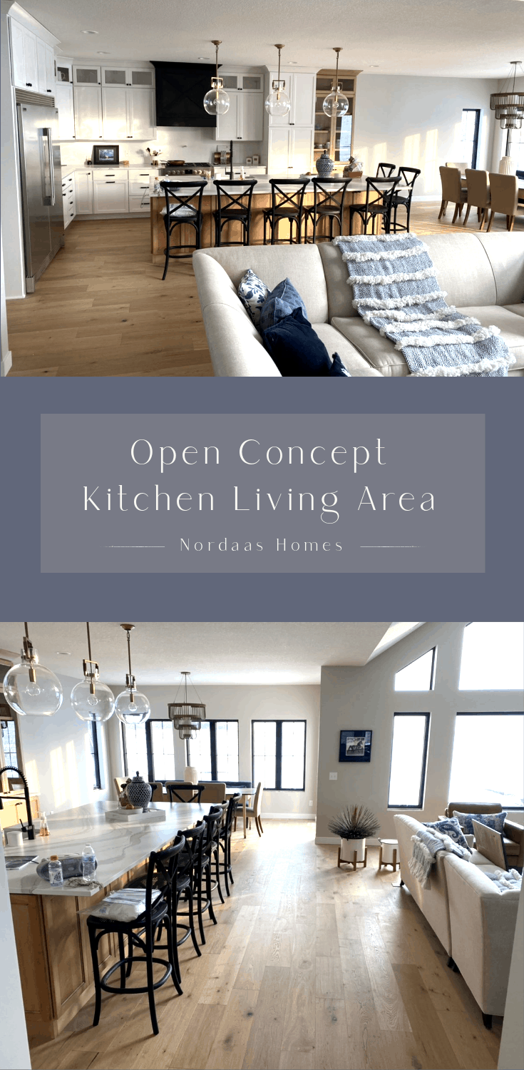 interior photo of open concept kitchen to living room area. traditional cabinets, large island, white oak flooring and huge windows make the space very open